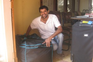 Amin (our tour guide) squatting next to the two bags of stuff we brought to the orphanage