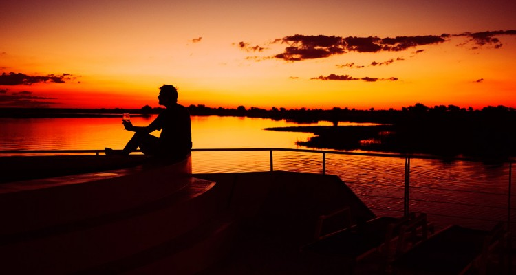 Silhouette of a man enjoying a sunset on the Chobe River, Botswana, Africa