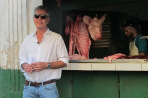Anthony Bourdain in front of butcher stand, Cuba