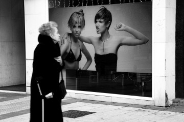 Old woman staring at black and white ad billboard in Madrid