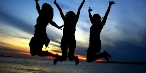 Three girls in silhouette jumping on beach in celebration