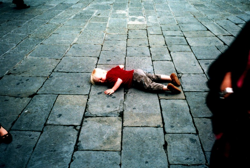 Child lying on ground outside