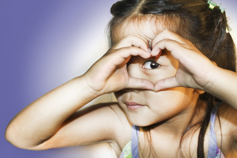 Young, compassionate girl making sign of heart with hands