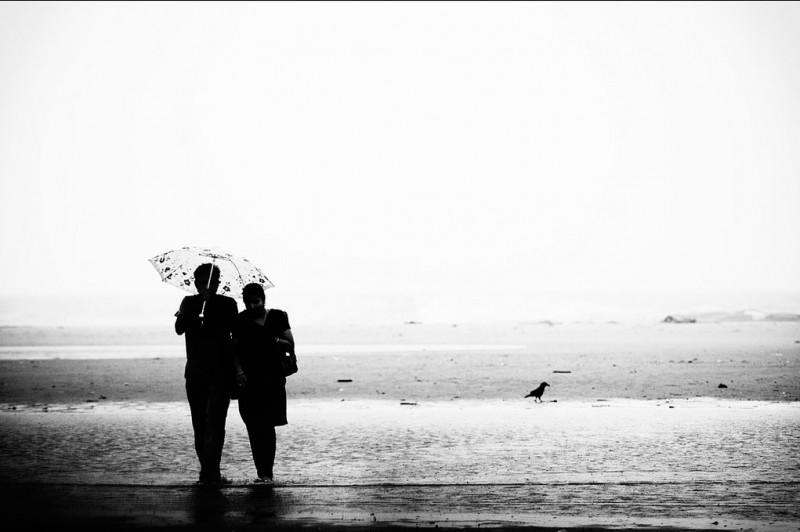 A couple walks the beach in Tamilnadu, India