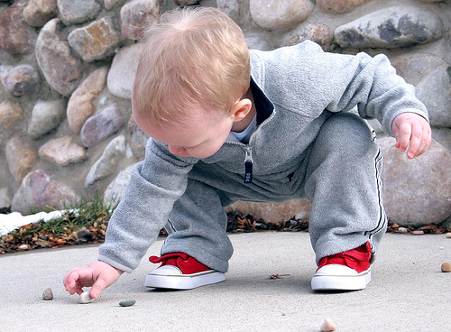 Young boy inspecting rock