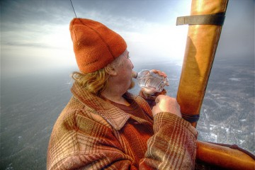 Man drinking in a hot air balloon over Helsinki, Finland
