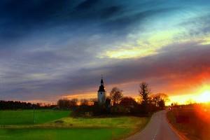 Sun sets behind the Färentuna church on Färingsö in Sweden