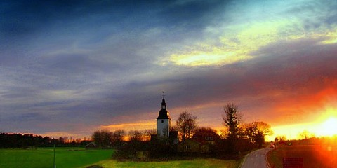 Sun sets behind the Färentuna church on Färingsö in Sweden