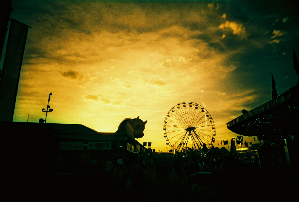 Giant cow and ferris wheel against omnious yellow sky, Arizona State Fair