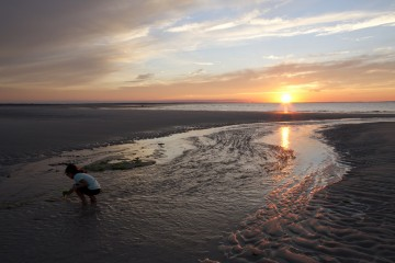 Young girl combing the beach at sunset in Cape Cod, Massachusetts