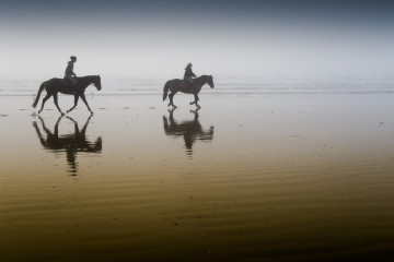 2 Girls Riding Horseback at Morro Strand State Beach, California