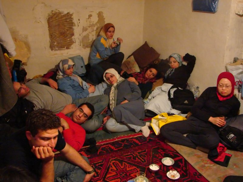 Group of houseguests/travelers relaxing on a floor
