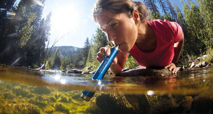 Woman using LifeStraw to purify water while traveling
