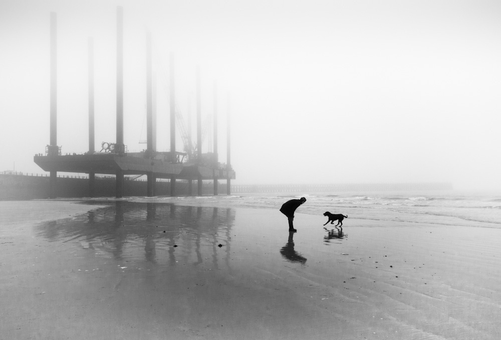 One man and his dog, Newhaven Beach, Sussex, UK