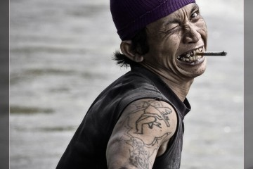 """Man in boat on Kayan River (Indonesia) with exaggerated """"pirate"""" expression"""