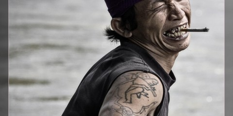 "Man in boat on Kayan River (Indonesia) with exaggerated ""pirate"" expression"