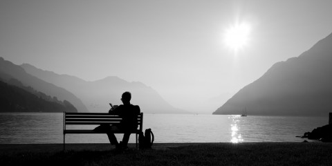 Man relaxing on a bench near a lake, Switzerland