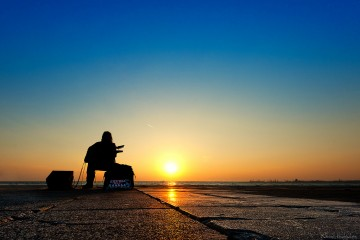 Man playing guitar alone while the sun sets in Thessaloniki, Greece