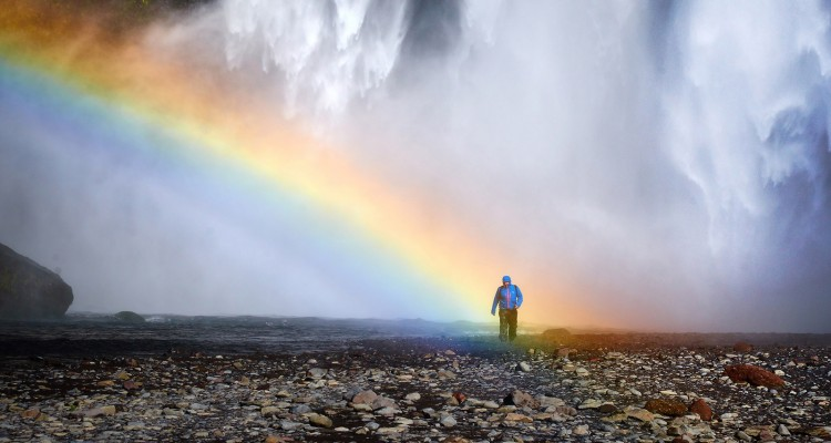 Man standing in rainbow light at Skogafoss Waterfall in Iceland