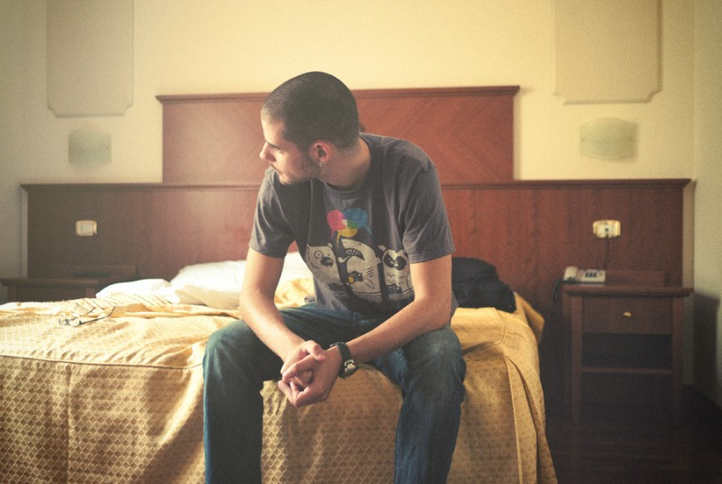 Man Sitting on Hotel Bed