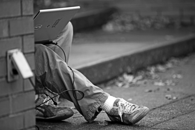 Man working on laptop in street in Portland, Oregon