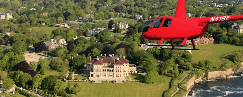 Red helicopter flying over the mansions of Newport, Rhode Island