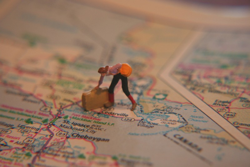 Miniature woman traveler figure standing on paper map