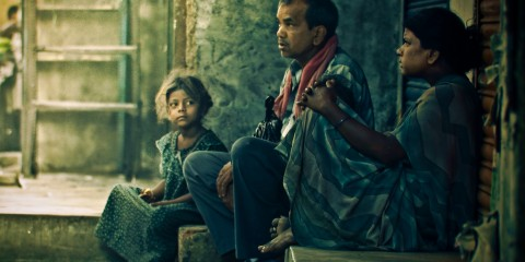 Indian family of three looking hopeful/pensive