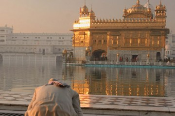 Man paying obeisance towards Golden Temple in Punjab, India