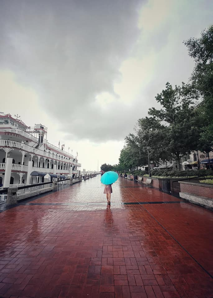 Kelsey walking along River Street in the rain in Savannah, Georgia