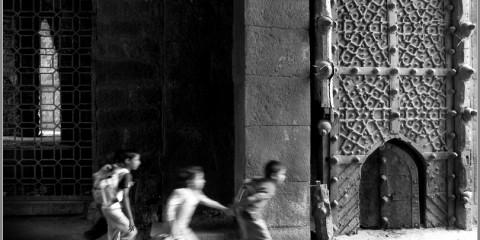 Children running through the gate of Golkonda Fort, Hyderabad, India