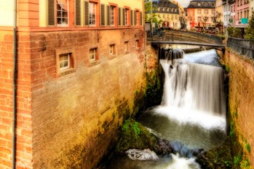 A river flows past an vintage building in Saarburg, Germany