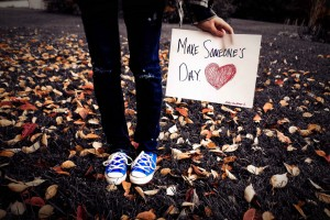 """Girl among leaves holding """"Make Someone's Day"""" sign"""