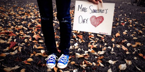 "Girl among leaves holding ""Make Someone's Day"" sign"