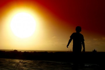 Silhouette of boy walking towards sun near Cartagena, Colombia