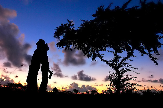 Two people standing against sunset backdrop