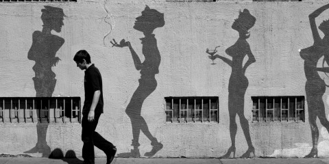 Man standing in front of street art silhouettes in Santiago, Chile