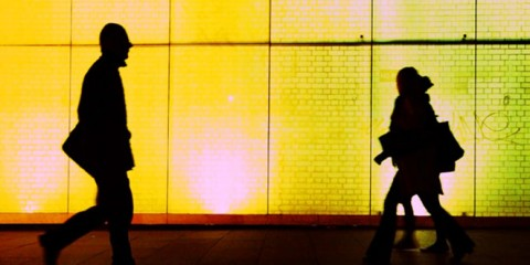Silhouette of two strangers passing