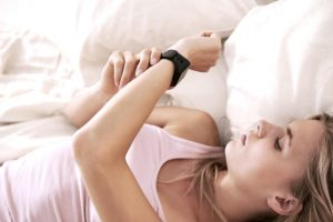 Girl lying in bed checking TomTom Spark 3