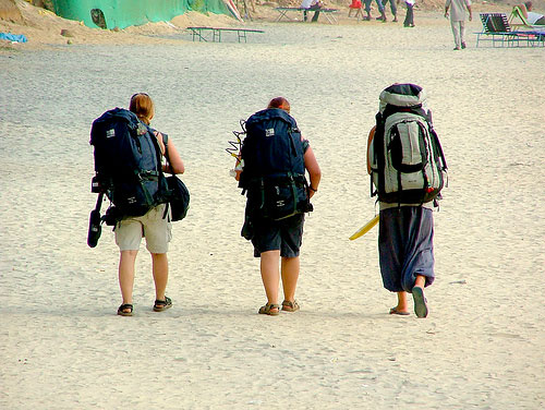 Three backpackers on beach in India