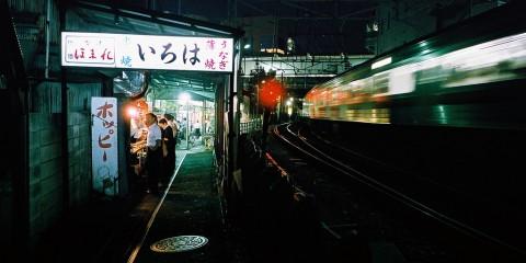 Men at food vendor near passing train in Kawasaki, Japan