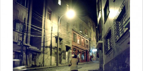Woman walking at night in streets of Valparaíso, Chile