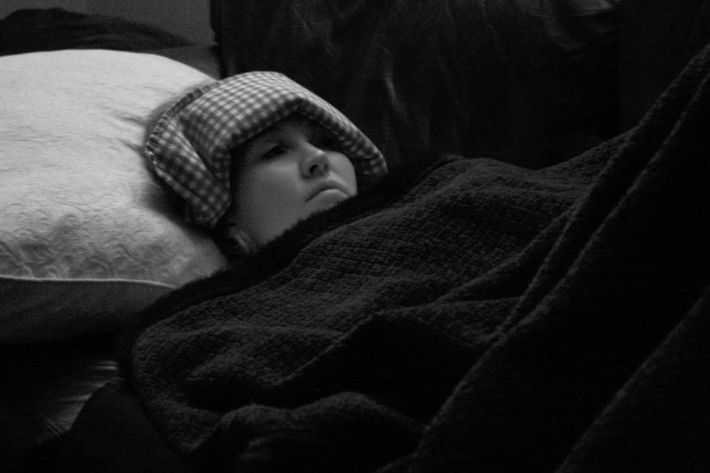 Woman with Migraine in Bed