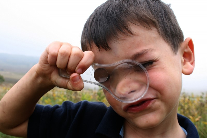 Young boy with magnifying glass smushed against face